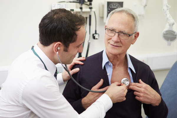 Doctor using a stethoscope on a patient.