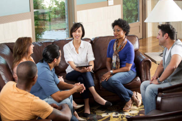 A support group meets to discuss their experiences.