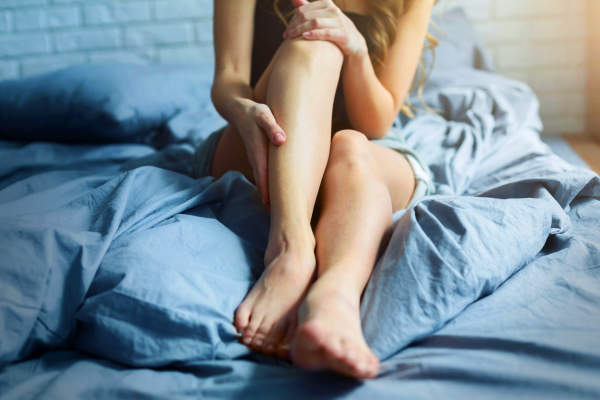 Woman with sore legs in bed