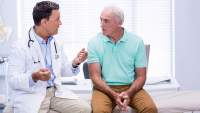 Senior man discussing treatment options for prostate cancer with his doctor.