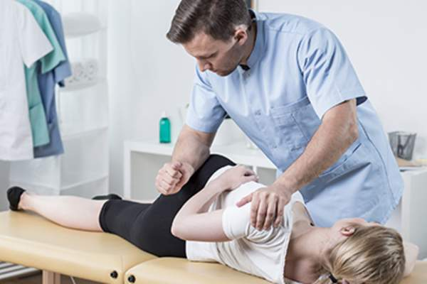 Chiropractor manipulating a woman's spine.