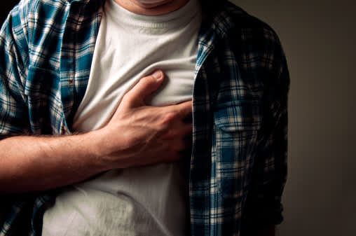Man clutches chest while experiencing a sharp pain.