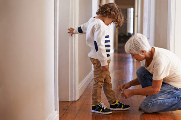 grandmother tying grandson's shoes in hallway