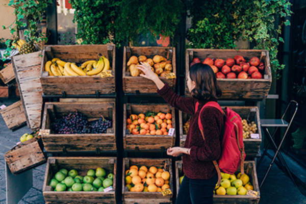 Woman picking out fresh fruit from a market.