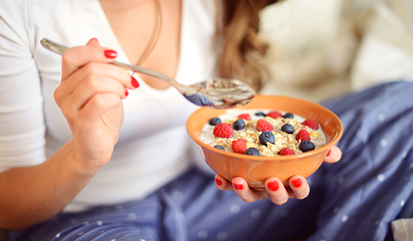 Woman in pajamas in bedroom eating muesli with berries.