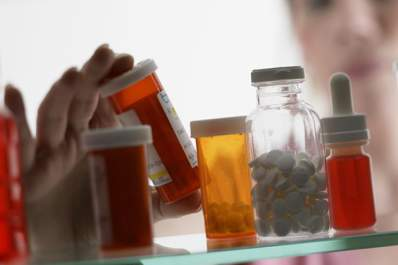 Woman looking at pills in medicine cabinet
