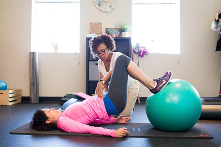 A woman works with a physical therapist for chronic pain.