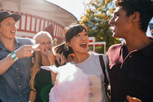 friends eating cotton candy at amusement park image