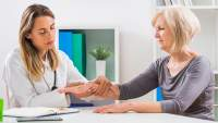 Doctor examining postmenopausal woman for osteoporosis.