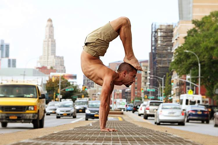 A man does yoga on a busy city street.