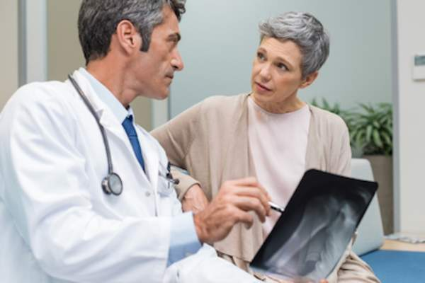 Doctor showing and explaining to patient her X-ray