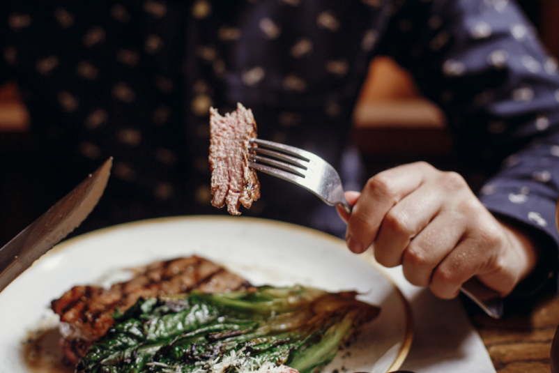Hands holding fork and knife and eating steak