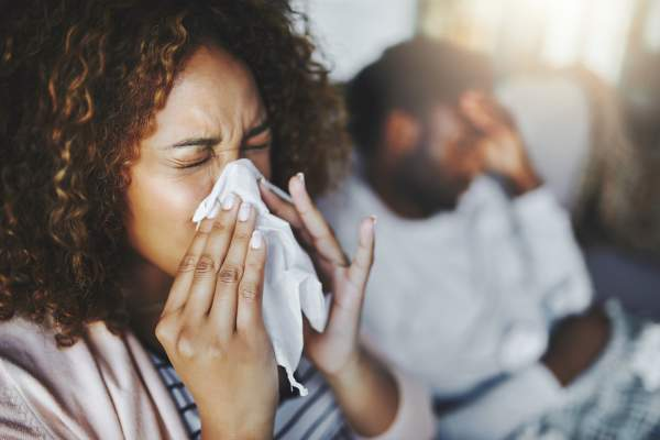 Woman sneezing and blowing nose into tissue
