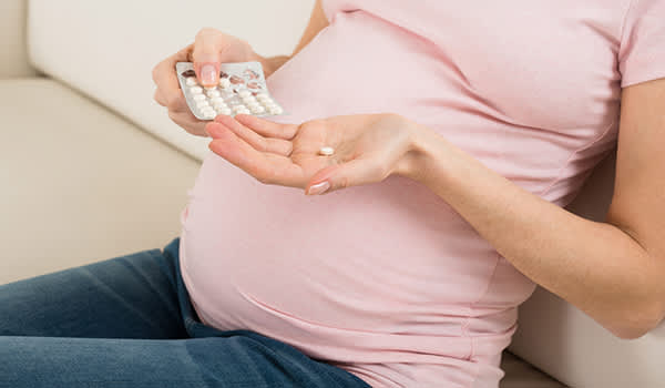 Pregnant woman taking a pill.