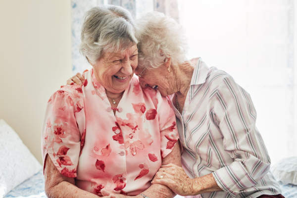 two senior women laughing and hugging