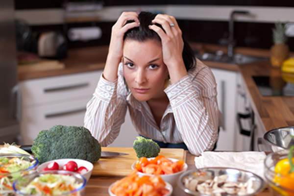A frustrated woman looking out at salad bowls in her kitchen.