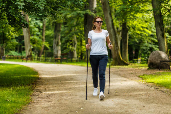 Middle aged woman walking with trekking poles in city park