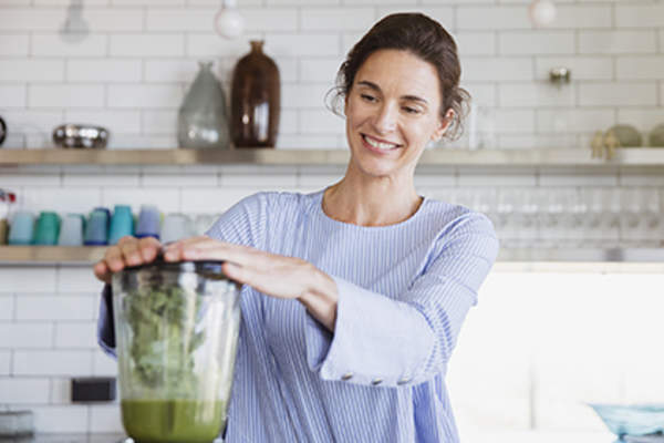 Woman using a blender in her kitchen to ease her psoriatic arthritis symptoms.