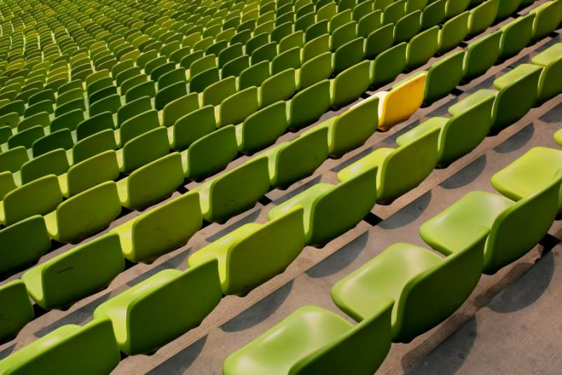 green chairs in a stadium with one yellow chair