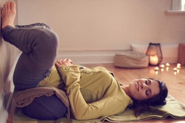 Woman practicing restorative yoga to prevent a psoriasis flare.
