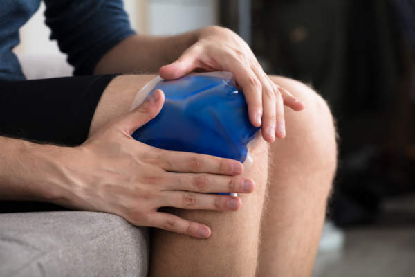 Person Sitting And Applying Ice Gel Pack On Knee