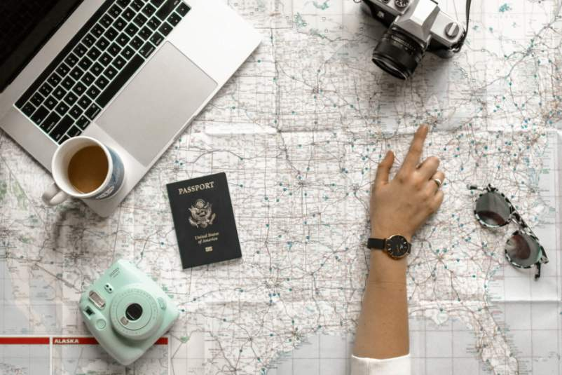 hand pointing out map surrounded by travel materials