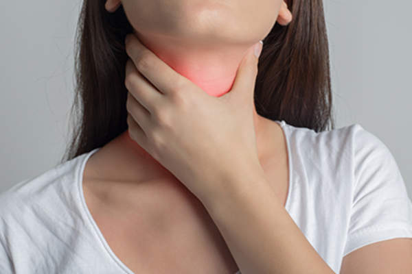 Woman holding her neck with throat, thyroid, or neck pain.