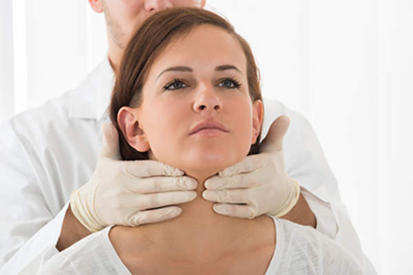 Doctor performing thyroid exam on woman.