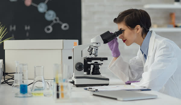 Female researcher looking through a microscope in laboratory.