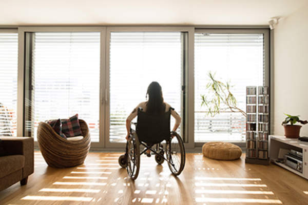 Woman in a wheelchair looking out the window.