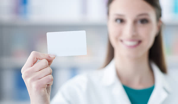 Pharmacist holding prescription discount card.