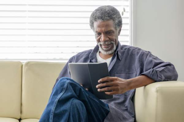 Man reading on couch in front of window.