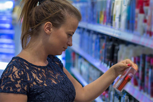 Young woman reading cosmetic label in store.