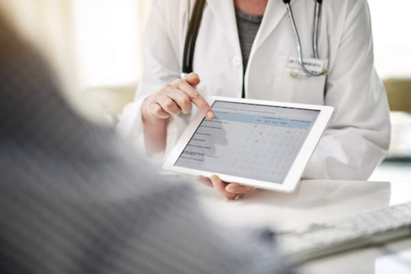 Doctor explaining treatment options to patient with tablet.