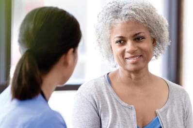 Smiling woman with diabetes talking to her doctor.