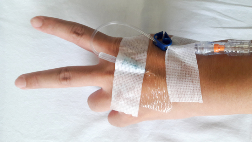 Patient hand with V sign and the tube of normal saline infusion on white cloth background.