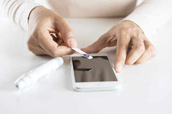 Entering blood glucose measurement into a smart phone.