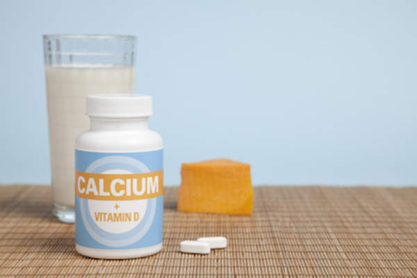Calcium and vitamin D supplements with milk and cheese in background.