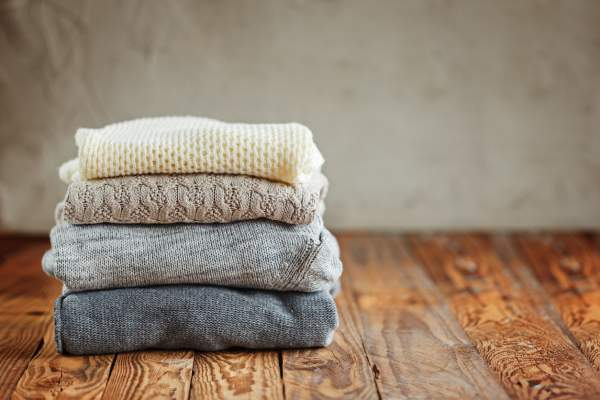 Stack of knitted wool winter sweaters on wooden background