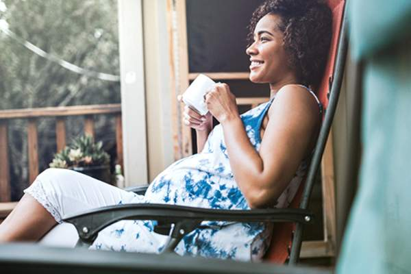 Smiling pregnant woman sitting on porch drinking tea image.