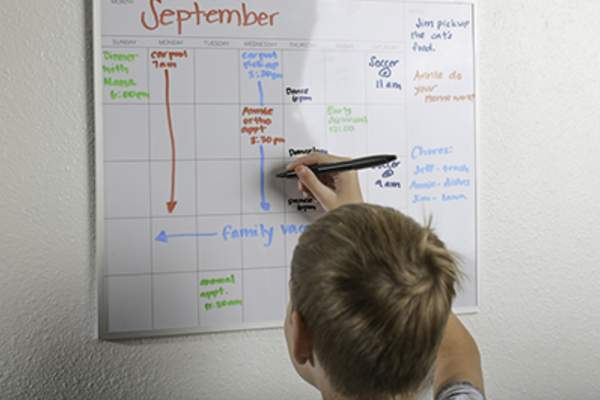 Boy drawing on whiteboard calendar