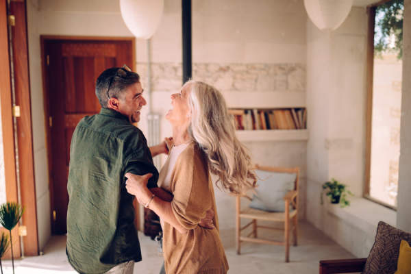 Happy senior couple dancing and laughing together at home