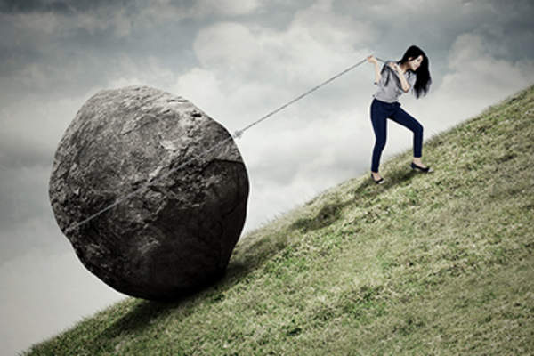 Woman pulling a boulder up a hill, long haul concept.