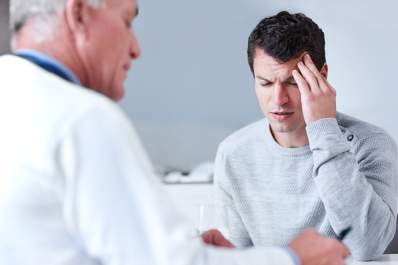 Man explaining his migraine to a doctor.