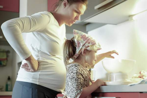 Pregnant mother and toddler preparing to make cookies.