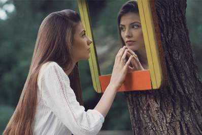 Young woman looking in mirror on tree outside, worried about aging.