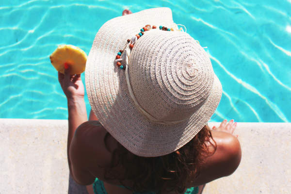 Woman in sun hat relaxing on vacation by the pool.