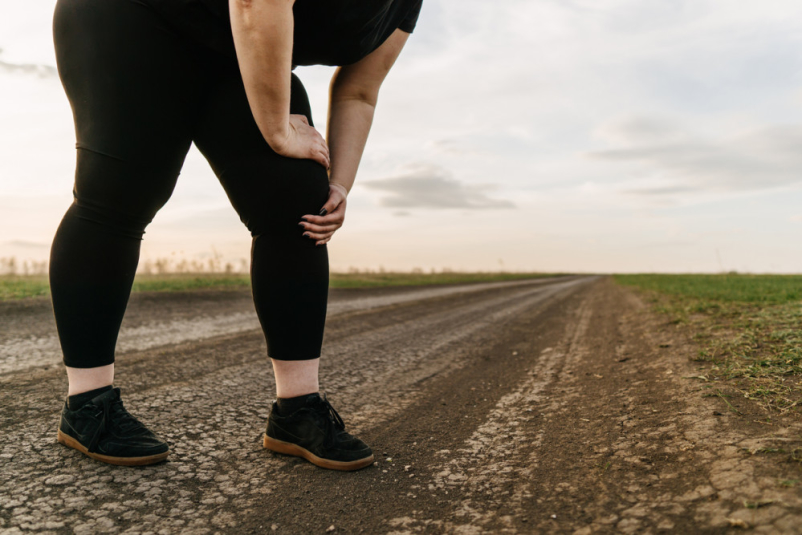 obese woman touching knee during run