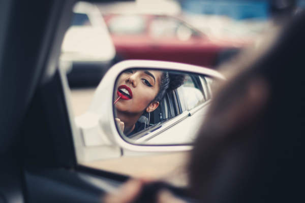 Woman putting on lipstick in car rearview mirror