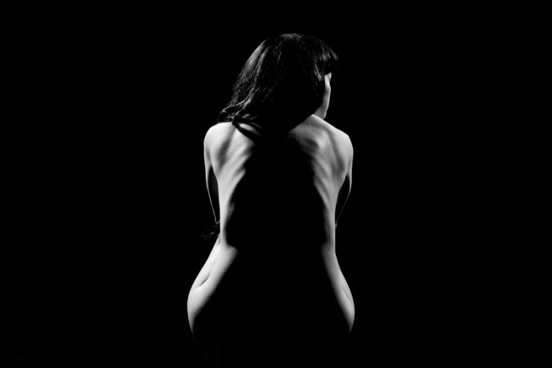 black and white photo of nude woman with shadow going down spine